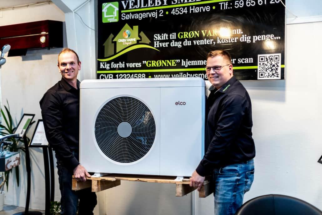 Vejleby VVS medarbejdere løfter en elco Luftvarme pumpe